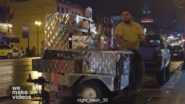 Hot dog vendor cooking food at night