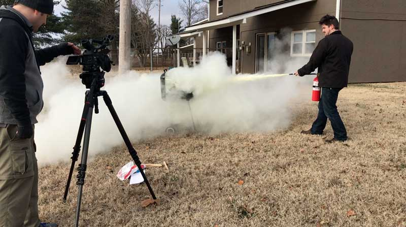 Man putting out fire with fire extinguisher during safety training video