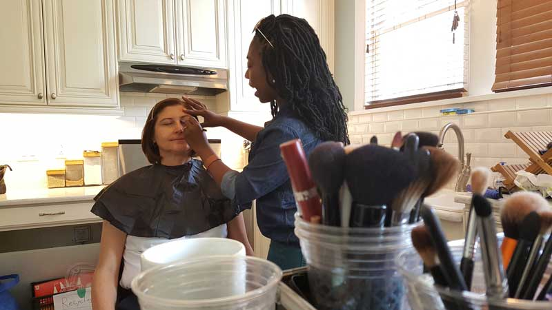 woman getting hair and makeup done before being filmed